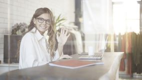 Businesswoman in glasses waving to the viewer royalty free stock photos