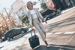 Businesswoman on the go. Full length of young woman in suit pulling luggage and smiling while walking outdoors stock photos
