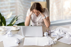 Businesswoman goes mad because of missing deadline. Desperate busy businesswoman sitting at desk covered crumpled paper. Woman in panic, fails in business, too Royalty Free Stock Photos