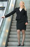 Businesswoman going down escalator Royalty Free Stock Image