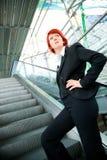 Businesswoman Going Up An Escalator Stock Photo