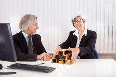 Businesswoman with gold bullion bars Royalty Free Stock Image