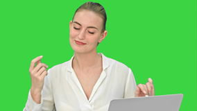Businesswoman in a good mood dance, sitting on the desk with laptop, and answer a phone call on a Green Screen, Chroma stock video