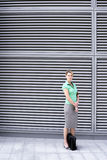 Businesswoman in green short-sleeved blouse and grey skirt standing on pavement, portrait Royalty Free Stock Photography