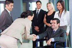 Businesswoman greeting partner. Young businesswoman greeting handicapped business partner and team Royalty Free Stock Photo