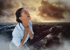 Businesswoman grieving in pain by ocean waves Stock Photos