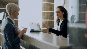 Businesswoman guest in hotel reception paying bill contactless payment credit card technology and talking with
