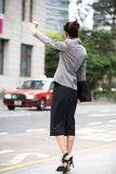 Businesswoman Hailing Taxi In Busy Street. Carrying Briefcase Stock Image