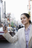 Businesswoman Hailing Taxi On Street. Beautiful young businesswoman with cell phone hailing taxi on city street Stock Image