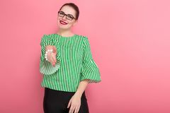 Businesswoman with hair bun. Portrait of attractive businesswoman with hair bun in striped blouse and eyeglasses giving hand for handshake on pink background royalty free stock photo