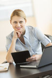 Businesswoman With Hand On Chin Holding Digital Tablet At Desk Royalty Free Stock Photography