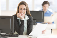 Businesswoman With Hand In Chin Sitting At Desk Royalty Free Stock Photography