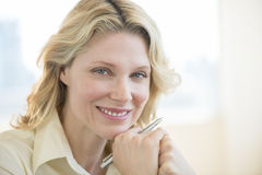 Businesswoman With Hand On Chin Smiling In Office Royalty Free Stock Photography