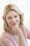 Businesswoman With Hand On Chin Smiling In Office Royalty Free Stock Photos