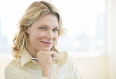 Businesswoman With Hand On Chin Smiling In Office Stock Images