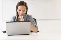 Businesswoman With Hand On Chin Using Laptop At Desk Stock Image