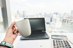 Businesswoman hand with coffee mug during tea break royalty free stock image