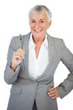 Businesswoman with hand on hip holding pen Royalty Free Stock Photo