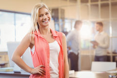 Businesswoman with hand on hip standing against male colleagues Stock Photo