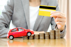 Businesswoman hand hold credit card, a toy car and a stack Royalty Free Stock Images