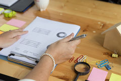 Businesswoman hand holding pen and analyzing business summary re Stock Images