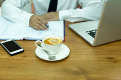 Businesswoman hand holding pen with cup of lemon tea and noteboo Stock Photos