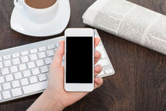 Businesswoman hand holding a phone with against the background o Royalty Free Stock Photos