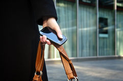 Businesswoman hand holding a phone and a bag. Businesswoman hand holding a phone and a brown bag Stock Image