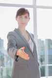 Businesswoman with hand out for handshake and smiling Stock Photo