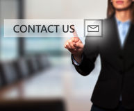 Businesswoman hand pressing contact us button on a touch screen. Interface. Women finger on mail icon.  on office. Business communication concept. Stock Image Royalty Free Stock Photo