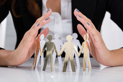 Businesswoman Hand Protecting Cut-out Figures Stock Photos