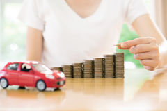 A Businesswoman hand pushing a toy car over a stack of coins Stock Photos