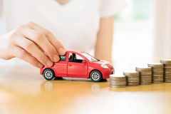 A Businesswoman hand pushing a toy car over a stack of coins Stock Photo