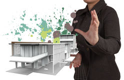 Businesswoman hand shows house model and splash colors Royalty Free Stock Images