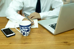 Businesswoman hand writing note with cup of coffee and notebook. Computer and cell phone on wooden table Stock Image