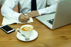 Businesswoman hand writing note with cup of lemon tea and notebo. Ok computer and cell phone on wooden table Stock Images