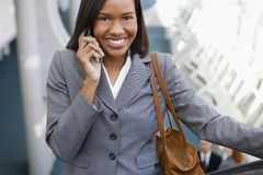 Businesswoman, with handbag, standing on escalator, using mobile phone, smiling, front view, portrait, elevated view Stock Images