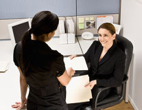 Businesswoman handing co-worker file folder. Businesswoman handing a co-worker a file folder Stock Images