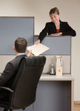 Businesswoman handing co-worker file folder. At desk in cubicle Royalty Free Stock Photography