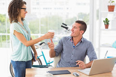 Businesswoman handing a mug of coffee to his colleague Royalty Free Stock Image