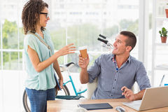 Businesswoman handing a mug of coffee to his colleague Stock Photos
