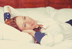Businesswoman with hands behind head lying in bed hotel room Royalty Free Stock Photo