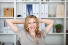 Businesswoman With Hands Behind Head In Office Royalty Free Stock Photo