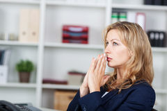 Businesswoman With Hands Clasped Looking Away In Office. Thoughtful mid adult businesswoman with hands clasped looking away in office Royalty Free Stock Image