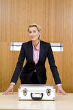 Businesswoman with hands either side of briefcase on conference table, portrait Royalty Free Stock Image