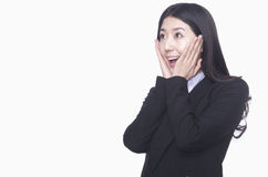 Businesswoman with hands on face acting surprised, studio shot Royalty Free Stock Images