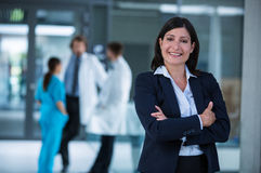 Businesswoman with hands folded. Portrait of a businesswoman standing with hands folded at the hospital premises Royalty Free Stock Images