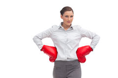 Businesswoman with hands on hips wearing boxing gloves Stock Photo