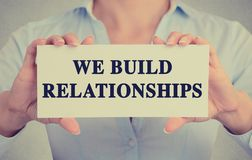 Businesswoman hands holding card with we build relationships message Stock Images