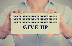 Businesswoman hands holding card with never give up sign message. Businesswoman hands holding white card with never give up sign message isolated on gray wall Royalty Free Stock Photos